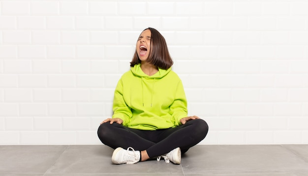 Spaanse vrouw die woedend schreeuwt, agressief schreeuwt, gestrest en boos kijkt