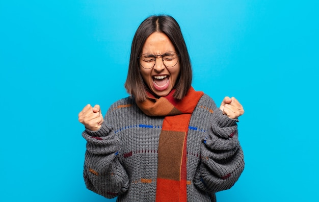 Spaanse vrouw die zich blij, verrast en trots voelt, schreeuwt en succes viert met een grote glimlach
