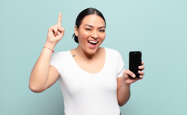 Spaanse vrouw die zich een blij en opgewonden genie voelt na het realiseren van een idee, opgewekt de vinger opstekend, eureka!