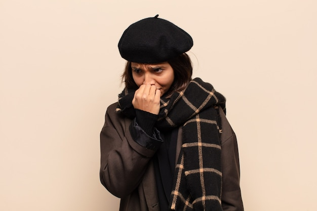 Spaanse vrouw die zich serieus, attent en bezorgd voelt, zijwaarts starend met de hand tegen de kin gedrukt