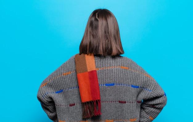 Spaanse vrouw die zich verward of vol voelt of twijfels en vragen, zich afvragend, met de handen op de heupen, achteraanzicht