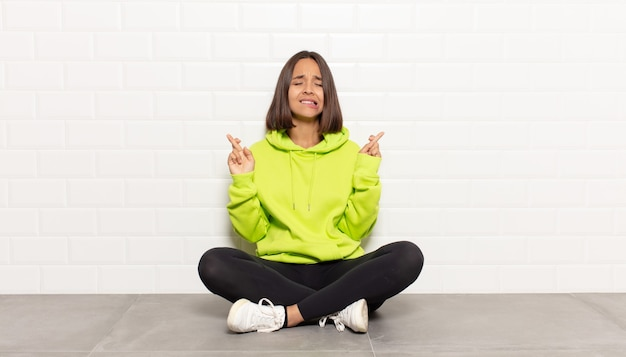 Spaanse vrouw glimlacht en kruist angstig beide vingers, voelt zich bezorgd en wenst of hoopt op geluk