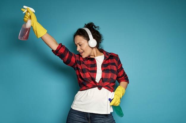 Spaanse vrouw, huisvrouw, met koptelefoon met reinigingssprays in haar handen en dansen met haar ogen dicht