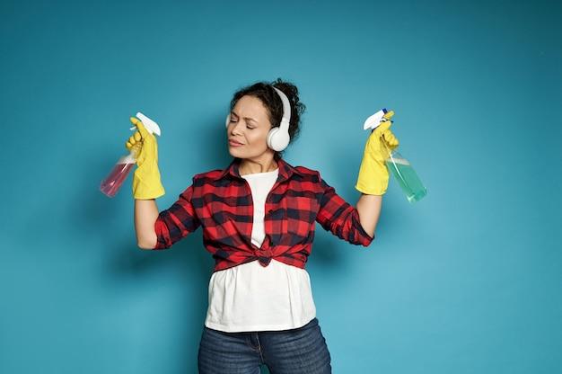 Spaanse vrouw, huisvrouw, met koptelefoon met reinigingssprays in haar handen en luistert naar muziek met haar ogen dicht