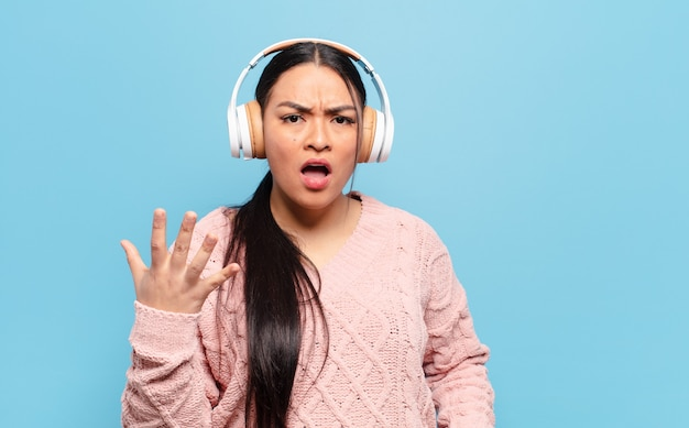 Spaanse vrouw kijkt boos, geïrriteerd en gefrustreerd schreeuwend wtf of wat is er mis met jou