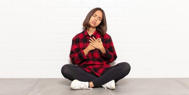 Spaanse vrouw kijkt verdrietig, gekwetst en diepbedroefd, houdt beide handen dicht bij haar hart, huilt en voelt zich depressief