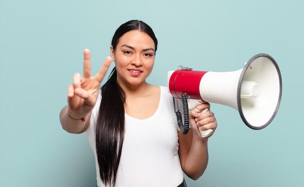 Spaanse vrouw lacht en ziet er gelukkig, zorgeloos en positief uit, gebarend overwinning of vrede met één hand