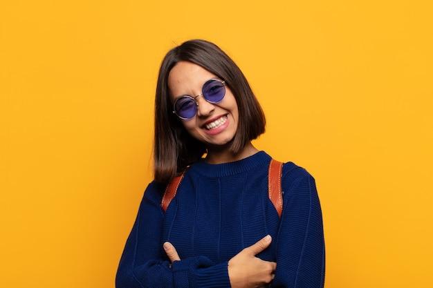 Spaanse vrouw lacht vrolijk met gekruiste armen, met een ontspannen, positieve en tevreden pose