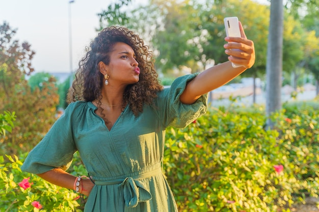 Spaanse vrouw met krullend haar op straat die grappige gezichten maakt en een selfie maakt met smartphone