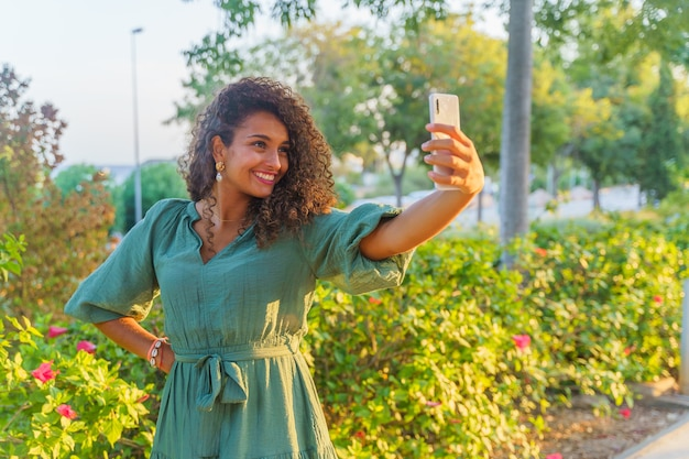 Spaanse vrouw met krullend haar op straat terwijl ze gelukkig is en een selfie maakt met een smartphone