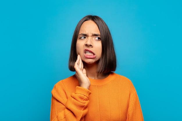 Spaanse vrouw met wang en pijnlijke kiespijn, zich ziek, ellendig en ongelukkig voelen, op zoek naar een tandarts
