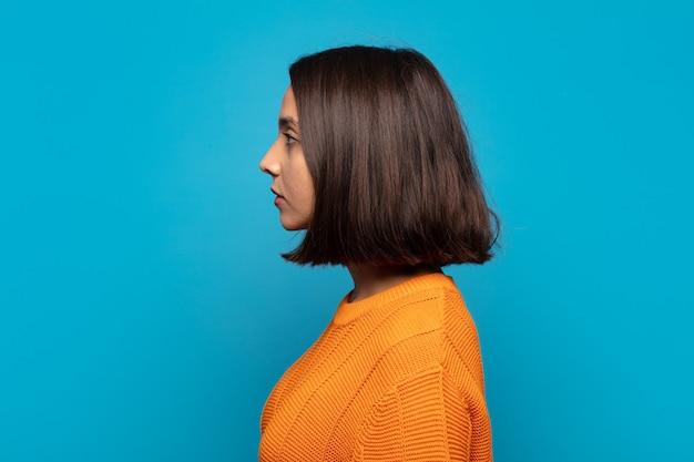 Spaanse vrouw op profielweergave die ruimte vooruit wil kopiëren, denken, zich voorstellen of dagdromen