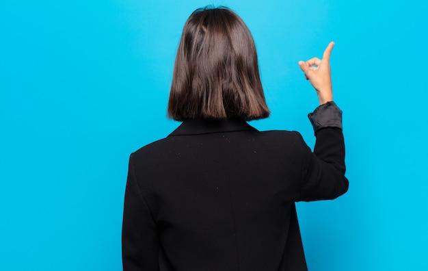 Spaanse vrouw staat en wijst naar object op kopieerruimte, achteraanzicht