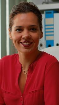 Spaanse vrouw typen op de computer en kijken naar camera glimlachen. ondernemer die werkt in een modern professioneel kantoor, werkplek in een persoonlijk zakelijk bedrijf, typt op pc-toetsenbord en kijkt naar desktop.
