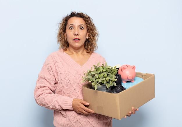 Spaanse vrouw van middelbare leeftijd die erg geschokt of verrast kijkt, starend met open mond en zegt wow