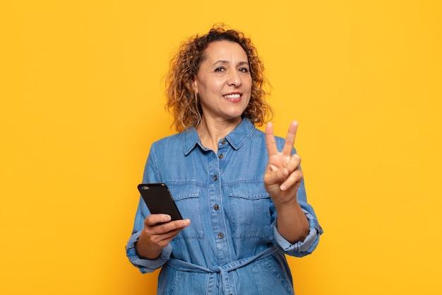 Spaanse vrouw van middelbare leeftijd die lacht en er gelukkig, zorgeloos en positief uitziet, gebarend overwinning of vrede met één hand