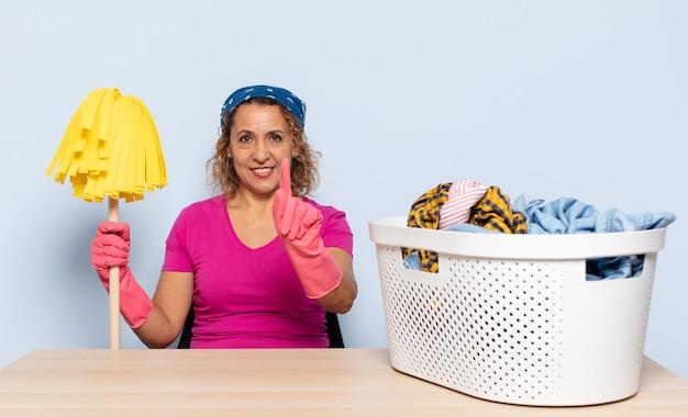 Spaanse vrouw van middelbare leeftijd die lacht en er vriendelijk uitziet, nummer één toont of eerst met de hand naar voren, aftellend