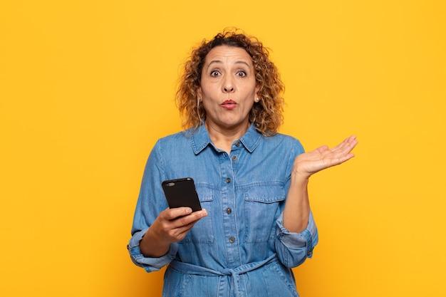 Spaanse vrouw van middelbare leeftijd die verbaasd en geschokt kijkt, met open mond een voorwerp vasthoudt met een open hand op de zijkant