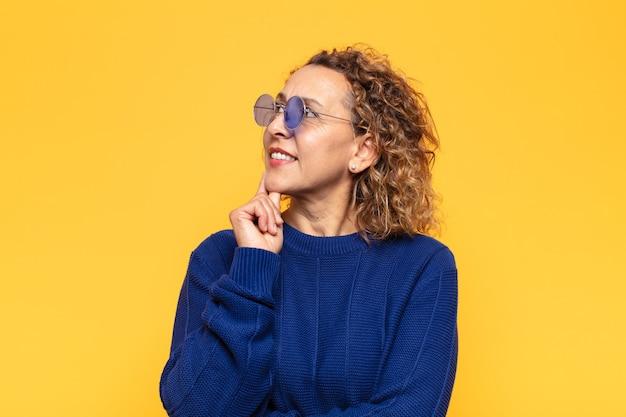 Spaanse vrouw van middelbare leeftijd die vrolijk lacht en dagdroomt of twijfelt, opzij kijkend