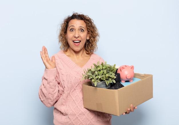 Spaanse vrouw van middelbare leeftijd die zich blij, opgewonden, verrast of geschokt voelt, glimlachend en verbaasd over iets ongelooflijks