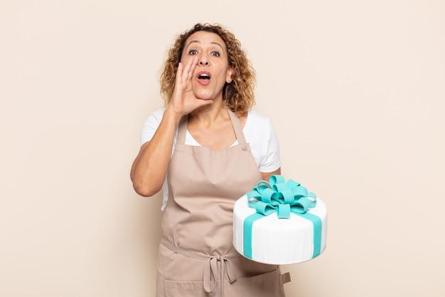 Spaanse vrouw van middelbare leeftijd die zich gelukkig, opgewonden en positief voelt, een grote schreeuw geeft met de handen naast de mond, roept