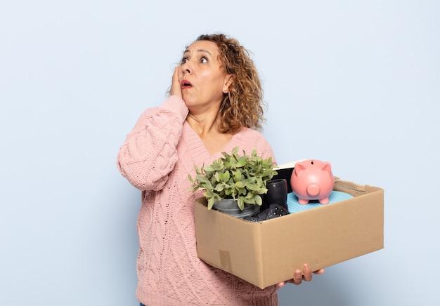 Spaanse vrouw van middelbare leeftijd die zich gelukkig, opgewonden en verrast voelt, opzij kijkend met beide handen op het gezicht