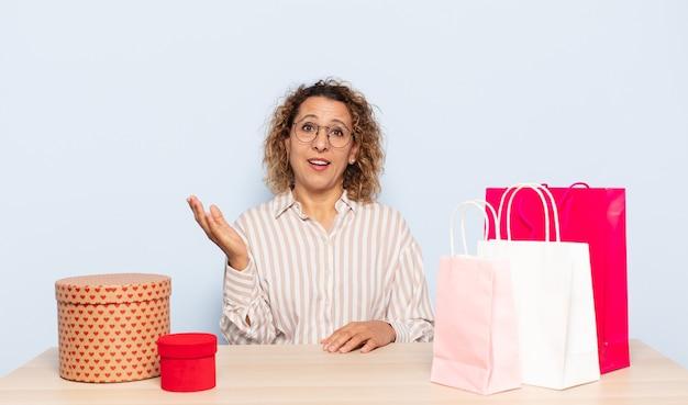 Spaanse vrouw van middelbare leeftijd die zich gelukkig, verrast en opgewekt voelt, glimlachend met een positieve houding, een oplossing of idee realiserend