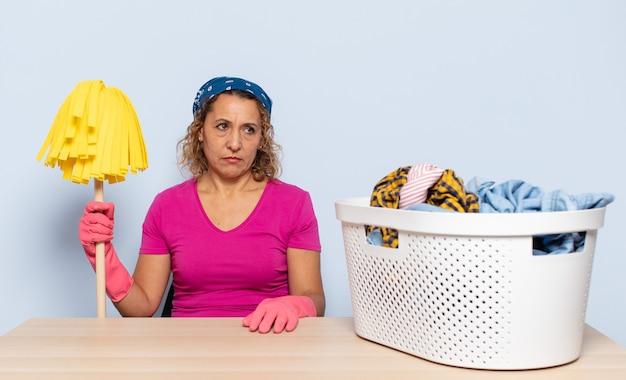 Spaanse vrouw van middelbare leeftijd die zich verdrietig, overstuur of boos voelt en opzij kijkt met een negatieve houding, fronsend in onenigheid