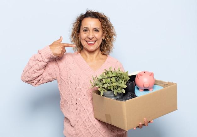 Spaanse vrouw van middelbare leeftijd glimlachend vol vertrouwen wijzend naar eigen brede glimlach, positieve, ontspannen, tevreden houding
