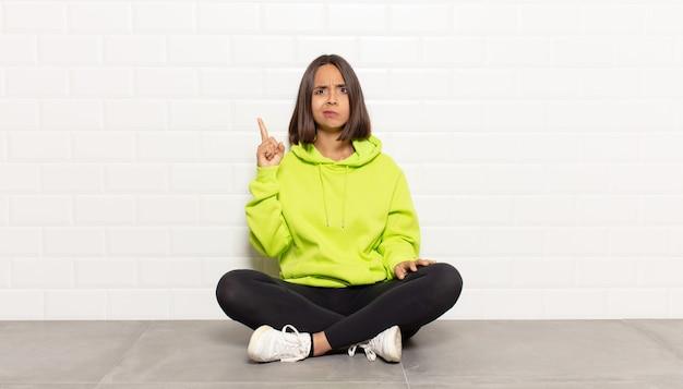 Spaanse vrouw voelt zich als een genie die trots haar vinger in de lucht houdt nadat ze een geweldig idee heeft gerealiseerd door eureka te zeggen