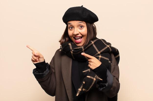 Spaanse vrouw voelt zich blij en verrast, glimlacht met een geschokte uitdrukking en wijst naar de zijkant