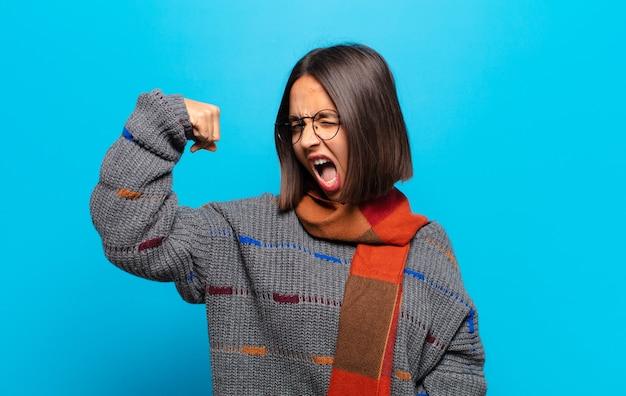 Spaanse vrouw voelt zich gelukkig, tevreden en krachtig, buigt fit en gespierde biceps, ziet er sterk uit na de sportschool