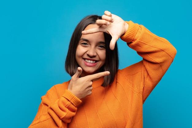 Spaanse vrouw voelt zich gelukkig, vriendelijk en positief, lacht en maakt een portret of fotolijst met handen