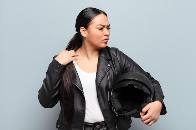 Spaanse vrouw voelt zich gestrest, angstig, moe en gefrustreerd, trekt de hals van het shirt aan en kijkt gefrustreerd door het probleem