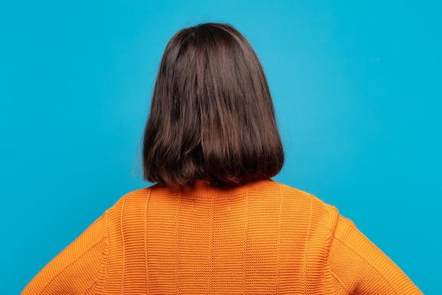 Spaanse vrouw voelt zich verward of vol of twijfels en vragen, zich afvragend, met de handen op de heupen, zicht naar achteren