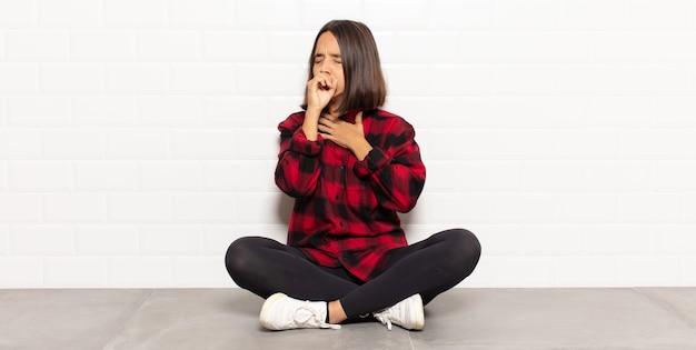 Spaanse vrouw voelt zich ziek met keelpijn en griepsymptomen, hoest met bedekte mond