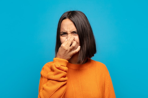 Spaanse vrouw walgt, houdt neus vast om te voorkomen dat ze een vieze en onaangename stank ruikt