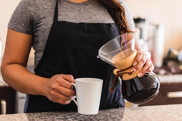Spaanse vrouwelijke barista koffie gieten