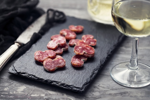Spaanse worst fuet op zwart keramisch bord