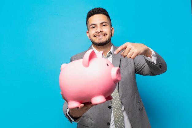 Spaanse zakenman die een spaarvarken wijst of toont en vasthoudt