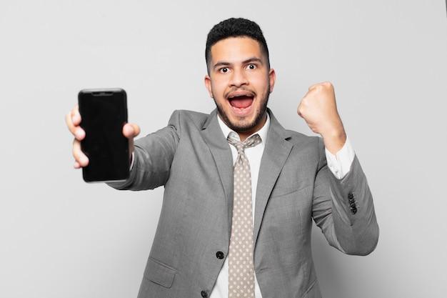 Spaanse zakenman die een succesvolle overwinning viert en een telefoon vasthoudt