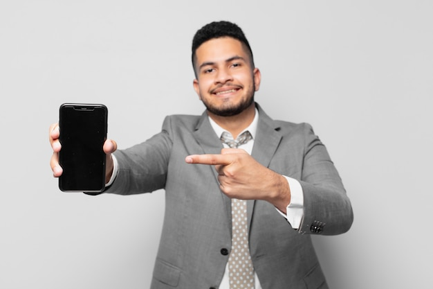 Spaanse zakenman die een telefoon aanwijst of toont en vasthoudt