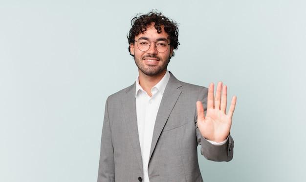 Spaanse zakenman die gelukkig en vrolijk glimlacht, met de hand zwaait, u verwelkomt en begroet, of afscheid neemt