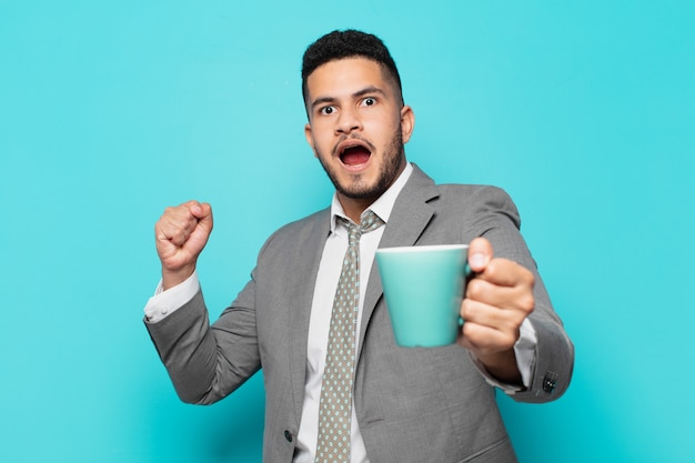 Spaanse zakenman die succesvol een overwinning viert en een koffiemok houdt