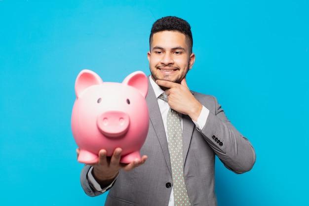 Spaanse zakenman die uitdrukking denkt en een spaarvarken houdt