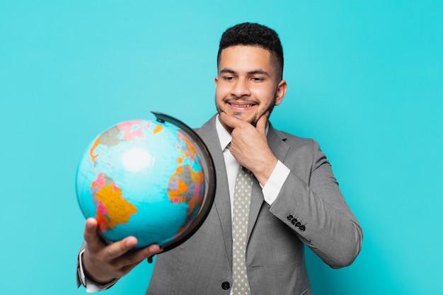 Spaanse zakenman die uitdrukking denkt en een wereldplaneetmodel vasthoudt