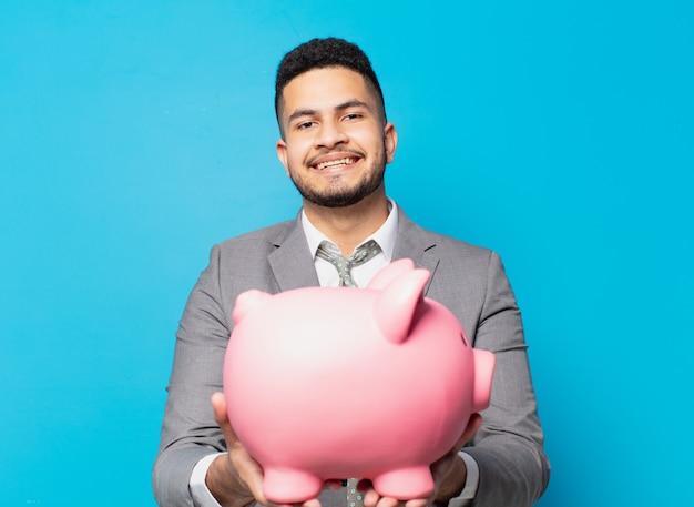 Spaanse zakenman gelukkige uitdrukking en houdt een spaarvarken