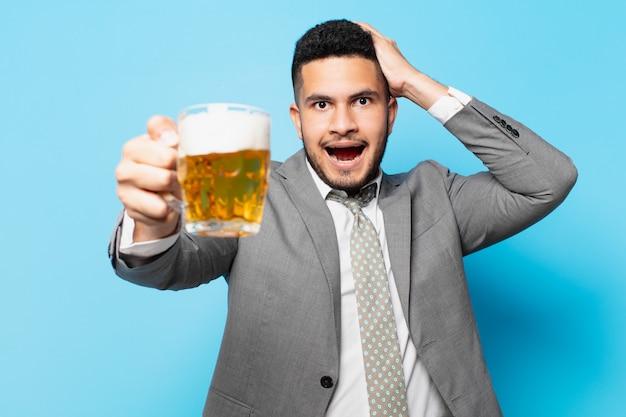 Spaanse zakenman verraste uitdrukking en houdt een biertje vast