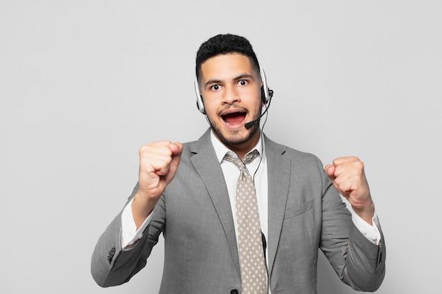 Spaanse zakenman viert succesvol een overwinning telemarketeer concept