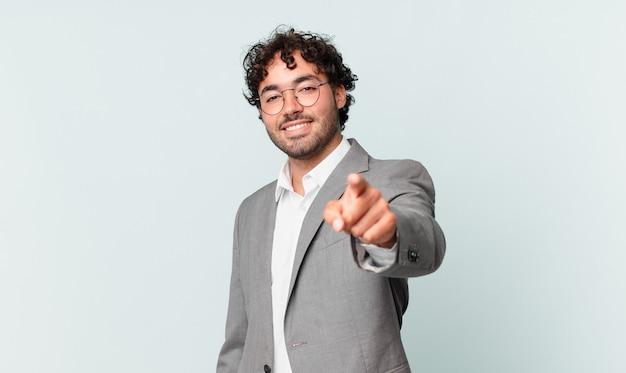 Spaanse zakenman wijzend op camera met een tevreden, zelfverzekerde, vriendelijke glimlach, jou kiezen